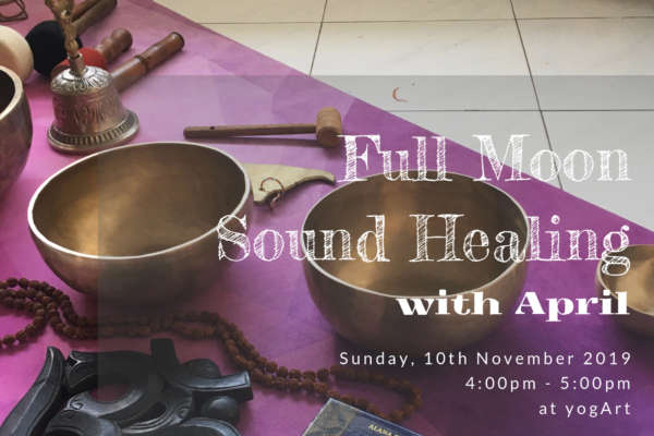 Tibetan singing bowls and sound healing tools scattered on top of a purple colored yoga mat