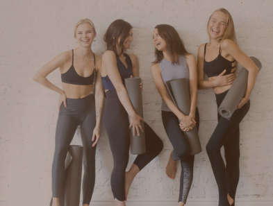 four women in sports attire leaning against a white wall in a line carrying a grey yoga mat smiling and posing