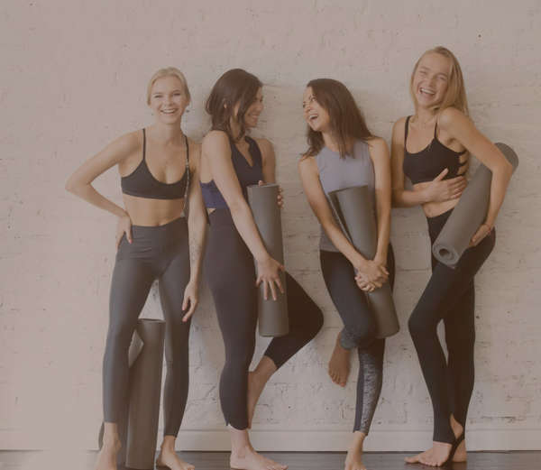 four women standing in line in sports attires leaning against a white wall carrying a grey yoga mat smiling and posing